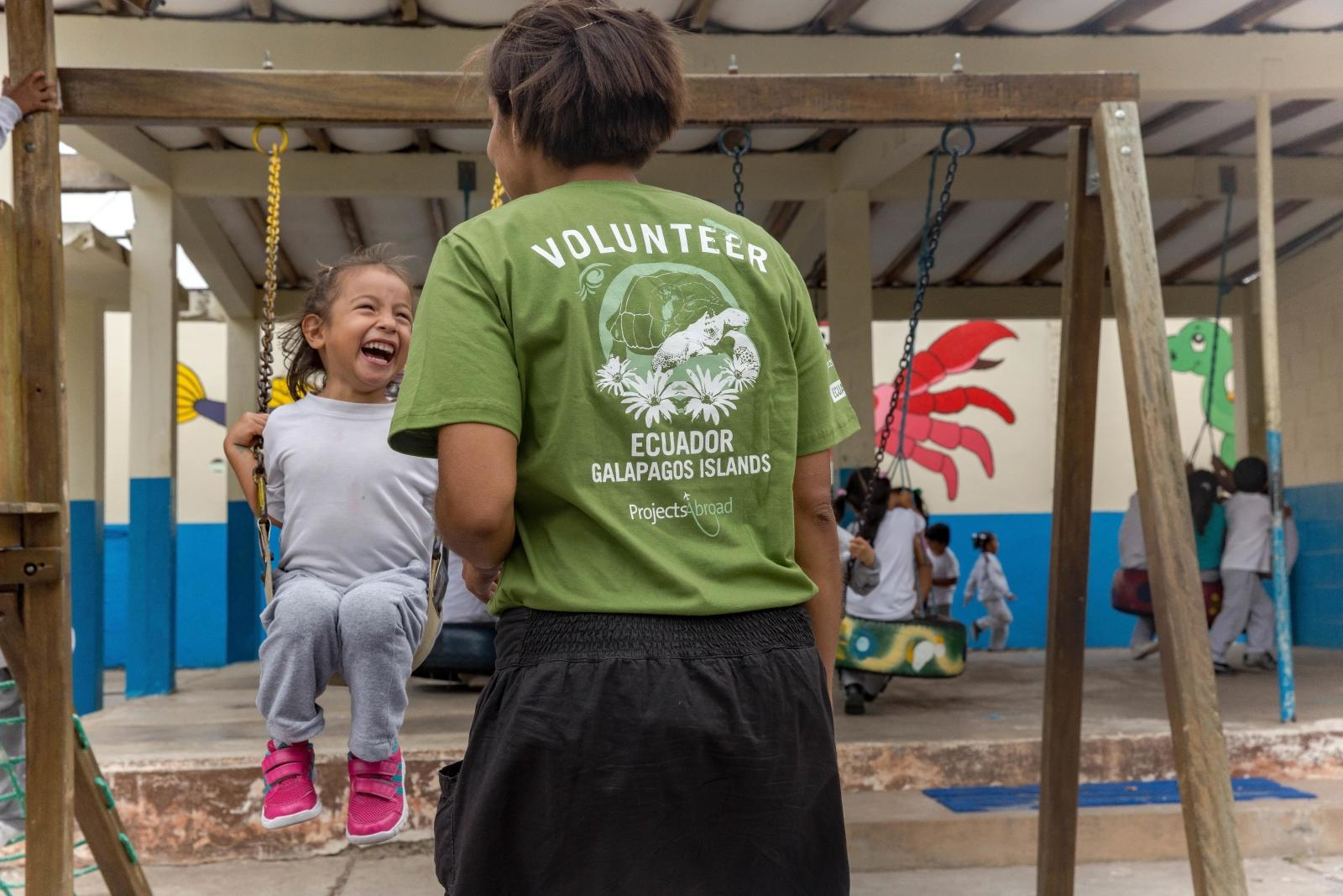 Volunteer and young girl play outside on a childcare project in Ecuador.